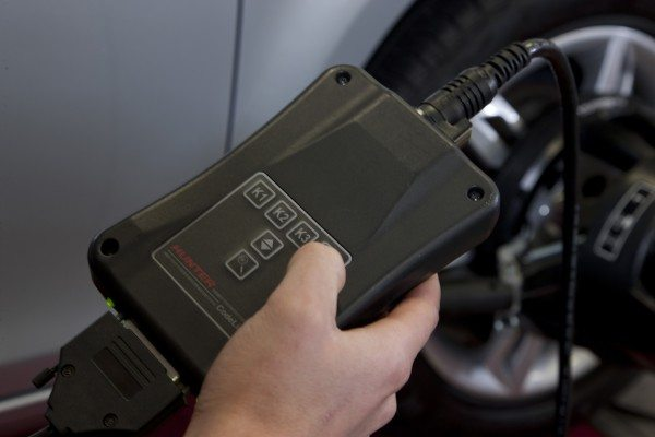 The CodeLink module plugs into the vehicle's OBD-II port and communicates directly with the alignment console