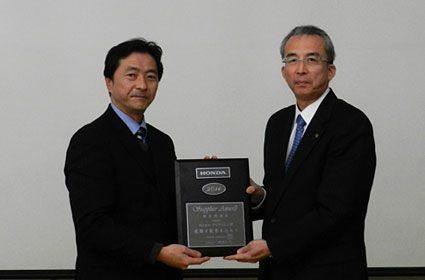 Honda's Hiroshi Saito (l) hands over the award to Yutaka Yamaguchi