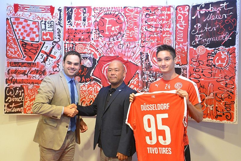 Fortuna Düsseldorf CEO Robert Schäfer shakes hands with Kenta Kuribayashi, president of Toyo Tires Europe. The pair are joined by player Justin Toshiki Kinjo