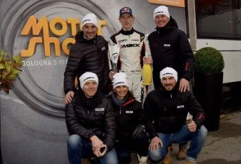 Elfyn Evans flanked by representatives of Dmack and Italy dealer OMPI Racing Tyres