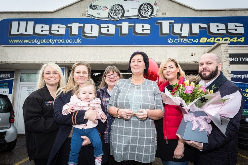 Jane Bailey (centre) receives her Foxy Lady Woman of the Year award (l-r) Ashleigh Warren, marketing manager, GT Radial Tyres, Jane's daughter Emma carrying granddaughter Felicity, Steph Savill, Foxy Lady Drivers Club, daughter Sophie, and Keith O'Brien, area sales manager Micheldever Tyres