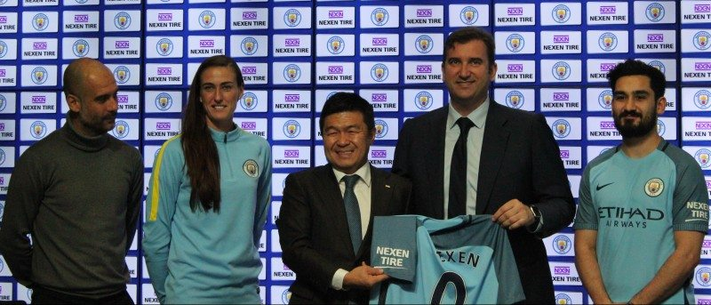 Nexen CEO Travis Kang (left of shirt) celebrates the signing with key Manchester City dignitaries and players including team manager Pep Guardiola (far right)
