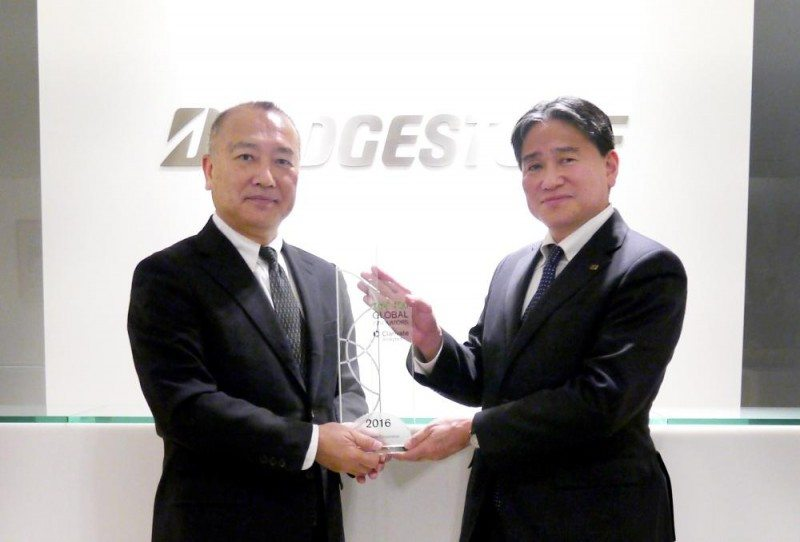 Clarivate Analytics' Hirofumi Hino (l) presents Mitsuru Araki, director of Bridgestone's Intellectual Property Division, with the award